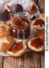 Delicious and healthy breakfast: fig jam and rolls close-up. vertical