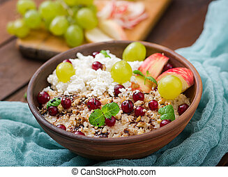 Delicious and healthy oatmeal with grapes, nuts, apples and cottage cheese. Healthy breakfast. Fitness food. Proper nutrition