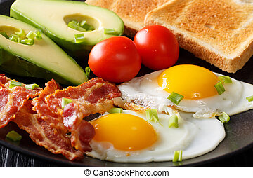 Delicious and hearty meal: two fried eggs with bacon, avocado, toast and tomato macro on a plate. horizontal