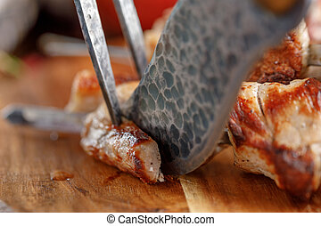 Delicious and juicy kebabs of pork on a wooden board that are cut with original cutlery for meat.