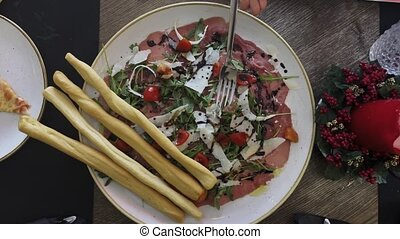 Close-up top view of having dinner at the restaurant. Eating appetizer with prosciutto, parmesan, rocket salad served with breadsticks aside