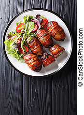 Delicious Armadillo eggs stuffed with jalapeno and cheese wrapped in bacon served with fresh salad close-up on a plate. Vertical top view