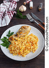Delicious Asian pilaf, stewed rice with vegetables and chicken drumstick on a plate. Wooden rustic background.