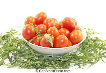 Delicious baby tomatoes and rocket in the plate isolated on white