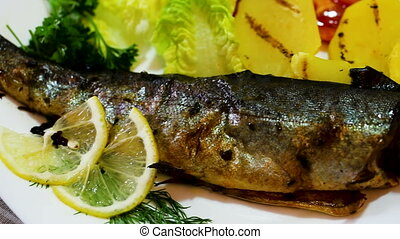 Delicious baked trout served on white plate with potatoes, ...