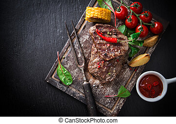Delicious beef steaks on wooden table, close-up.