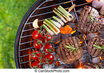 Delicious beef steaks with vegetable on a barbecue grill.
