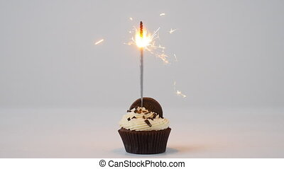 Delicious birthday cupcake with burning sparkler on white table