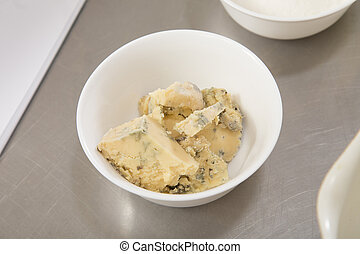Delicious blue cheese in a white ceramic bowl.