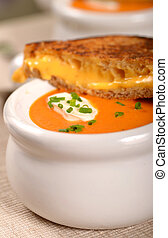 Delicious bowl of tomato soup with grilled cheese sandwich -...