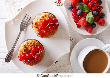 Delicious breakfast, coconut muffins, berries and coffee with milk close-up on the table. Horizontal top view