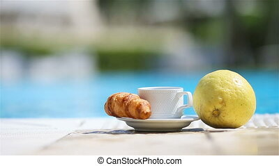 Delicious breakfast lemon, coffee, croissant by the pool -...
