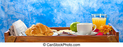 Delicious breakfast on tray consisting of coffee, orange juice, apple, croissants, jam and butter with newspaper lying on the side