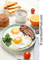 Delicious breakfast or lunch with fried eggs on wooden background, close up