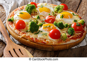 Delicious breakfast: pizza with eggs, broccoli, tomatoes and herbs close-up. horizontal