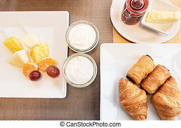 Delicious Breakfast top view fresh croissant, fruits and yogurt. Still life of sweets and fruits top view.