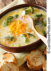 Delicious broccoli cheddar cheese soup in a bowl with toasted bread closeup. vertical