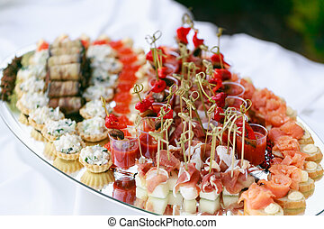 Delicious bruschetta with salmon and canape shrimp on table. Tasty buffet table. Summer party outdoor. Catering concept