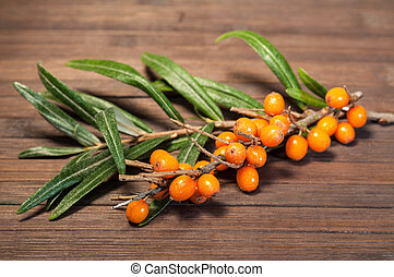 Delicious buckthorn on a brown cutting board