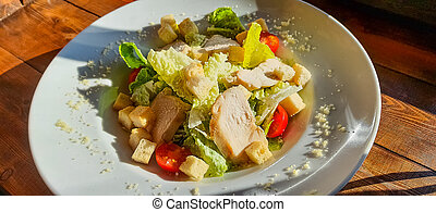 Delicious Caesar salad with roasted chicken meat. Fresh Vegetable salad with chicken , tomatoes, cheese. Fresh healthy salad on wooden table. Top view.