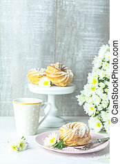 Delicious cake with coconut chips on pink  plate on white table, autumn white chrysanthemum and cup of coffee
