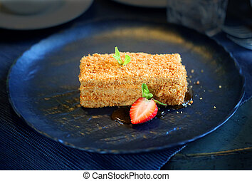 Delicious cake with honey and strawberries on plate