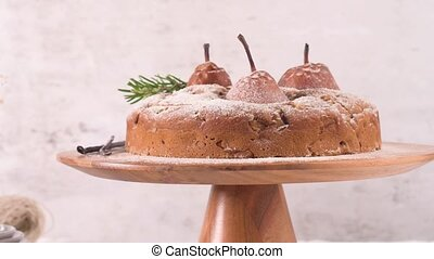 Delicious cake with pear, ginger and cinnamon on a dark kitchen counter.