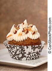 Delicious carrot cake cupcake with cream chees frosting and chopped pecan nuts
