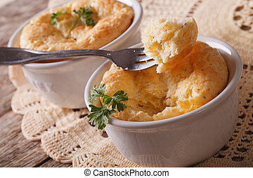 Delicious cheese souffle in white ramekin close-up. ...