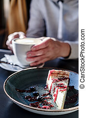 Delicious cheesecake, with fresh berries on a plate, against the background of hands holding a cup of cappuccino, in natural light