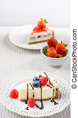 Delicious cheesecake with strawberry on a table against white wall.