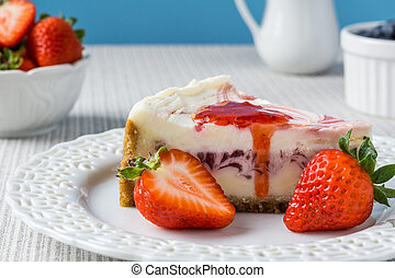 Delicious cheesecake with strawberry on a table against blue wall.