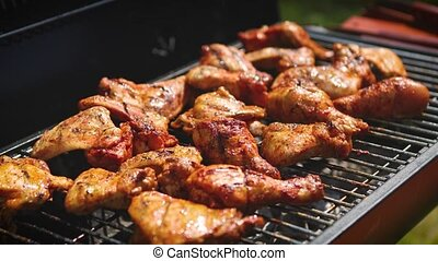 Delicious chicken pieces frying on barbecue grill. Outdoor...