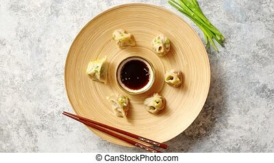 Delicious chinese dumplings served on wooden plate with...