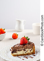 Delicious chocolate cheesecake with strawberry on a table against white wall.