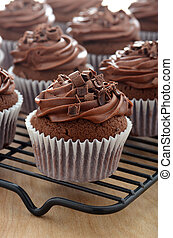 Delicious Gourmet Chocolate Cupcakes with chocolate frosting and shaved chocolate chunks cooling on a rack