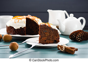 Delicious chocolate fruit cake ornated with cream icing and orange peel served with tea, nuts, cones and cinnamon sticks on blue background