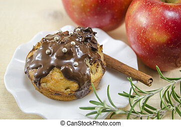 Delicious chocolate muffin with two apples in the background