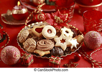 Detail of delicious Christmas cookies with candles in red tone