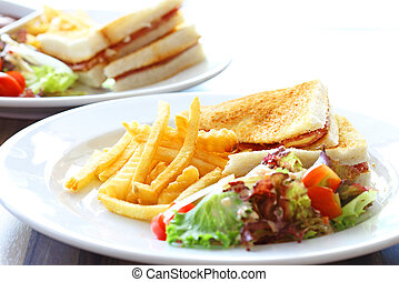 Delicious club sandwich with french fries and salad