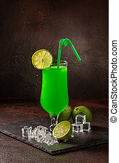 Delicious cold refreshing smoothie drink in cocktail glass with lime and mint
