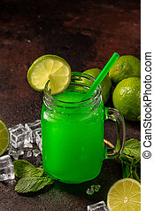 Delicious cold refreshing smoothie drink in cocktail glass with lime