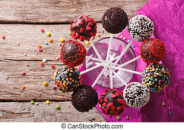 Delicious colorful cake pops in a glass. Horizontal top view...