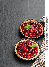 Delicious cranberry tarts in baking mold on black stone background