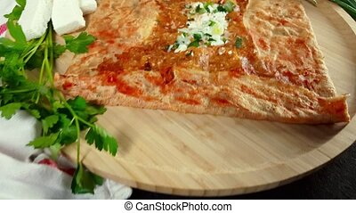 Presentation of delicious crepe with cheese served with appetizers and tea on a wooden board on a black background