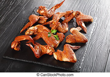 chicken wings on a black stone plate