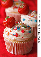 upcakes with cream and fresh strawberries close up. vertical