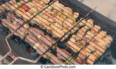 Delicious different kinds of meat with vegetables cooked on smoldering coals on a barbecue outdoors