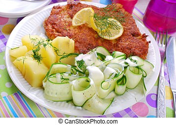 delicious dinner with pork chop and cucumber salad