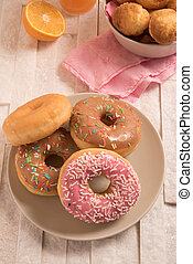 Delicious donuts with icing in a plate on marble background